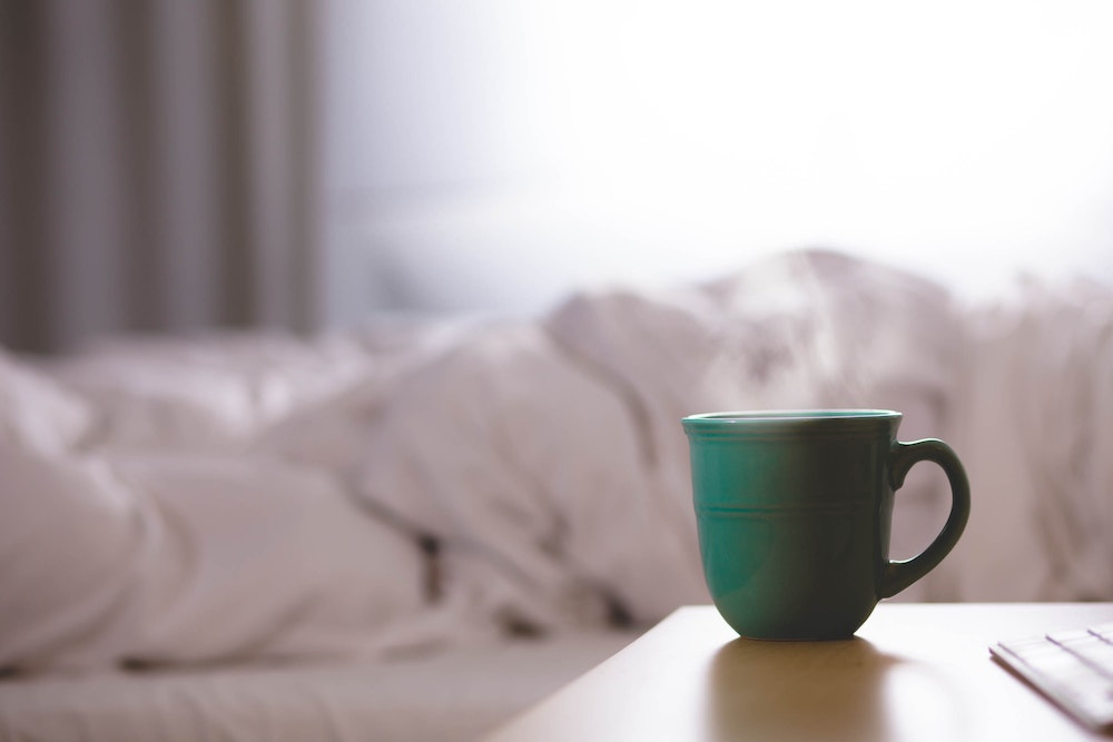 Cup of coffee and bed sheets